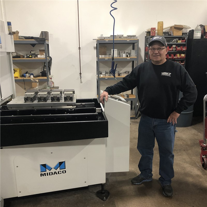 Man in black sweatshirt, blue jeans and black ball cap standing in his machine shop with his right hand resting on a Midaco Pallet Changer machine with a rectangualr aluminum pallet and vices with parts on the pallet changer shuttle
