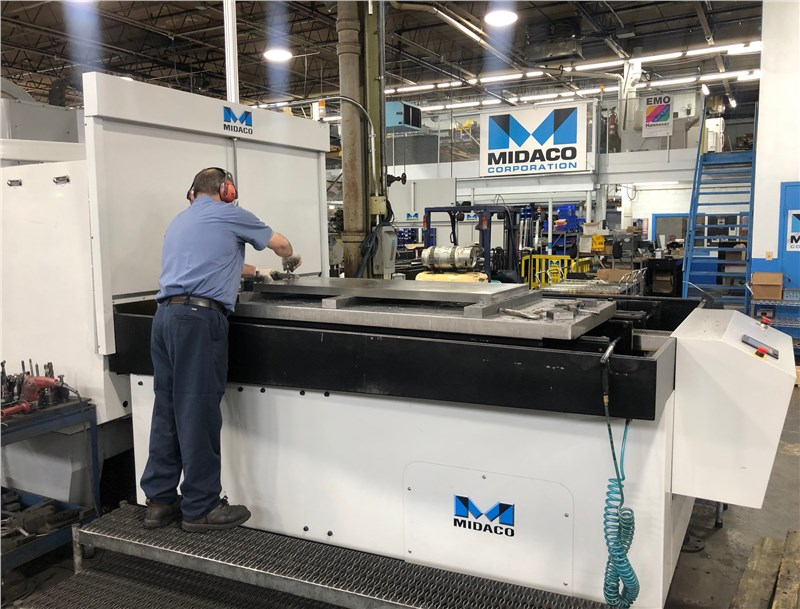 Machinist working on Midaco Pallet Changer with parts mounted to machining center table 2