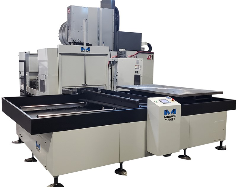 """three quarter view of large grey and black Midaco brand Automatic Pallet changer with blue Midaco """"M' logo mounted on Haas VS1 machining center on plain white background."""
