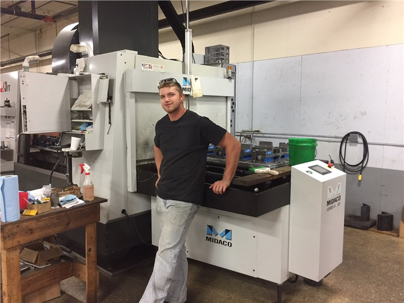 Marcus Mullet leaning against a Midaco Automatic Pallet Cahnger in his machine shop