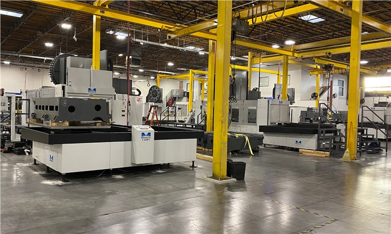 Multiple Midaco Pallet Changers on CNC Machining Centers Haas Factory floor with bright yellow steel posts in the factory