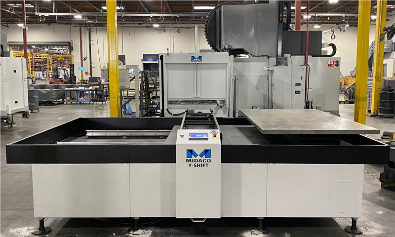 Front view of Midaco Pallet Changer mounted on Haas VS1 machinig center showing factory ion the background