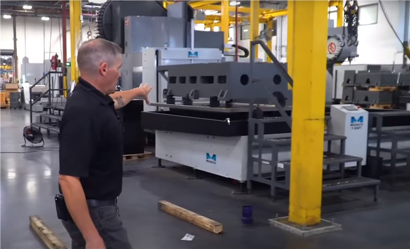 Man in black shirt and blue jeans walking the HAAS factory floor giving a tour showing Midaco pallet changers and HAAS machining centers in the background