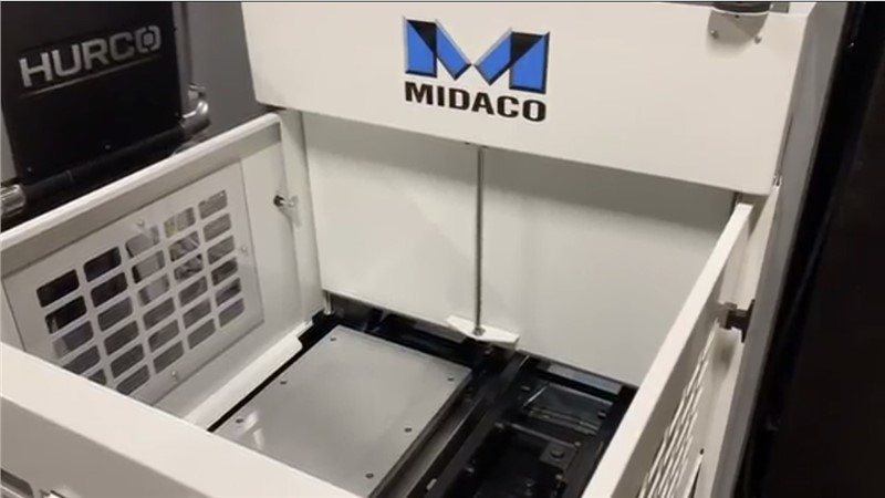"Dove grey color Midaco pallet changer shuttle system with blue M logo showing one 22""x16"" aluminum pallet on the shuttle system. HURCO logo on machining center in bacgground"