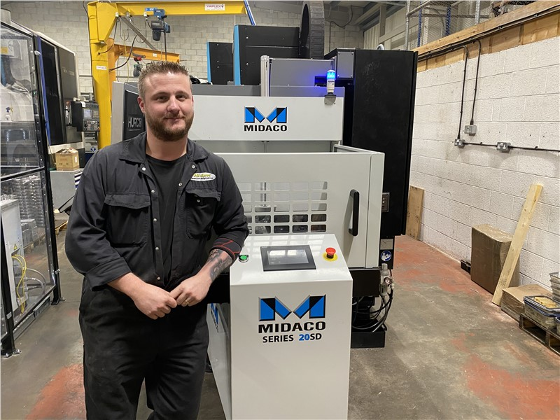 """Man wearing a dark machine shop jumpsuit uniform standing next to grey color Midaco pallet changer shuttle system with blue M logo showing one 22""""x16"""" aluminum pallet on the shuttle system. HURCO logo on machining center in background"""