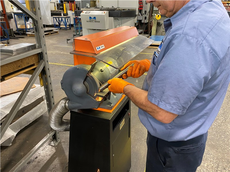 Operator grinding part on bench grinder with orange protective shield in machine shop