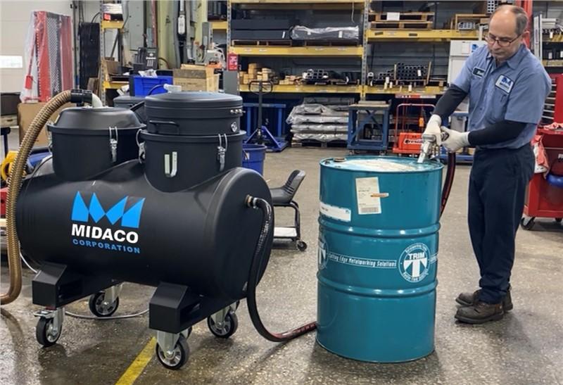 Machinist removing CNC liquid from industrial vacuum into disposal drum