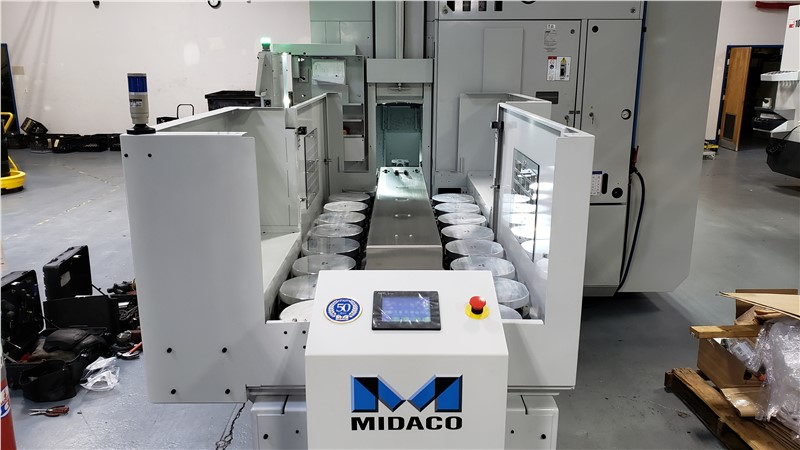 Front view showing inside of MIDACO Automatic Multi-Pallet Changer round aluminum pallets loading into the side of a 5-Axis machining centerounted