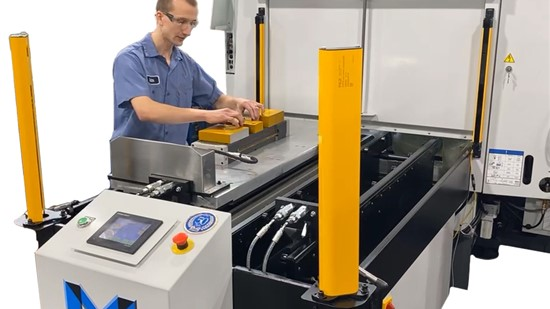 Machinist placing parts in workholding vices powered by the MIDACO Hydraulic Docking System on an Automatic Pallet Changer mounted to a VMC.