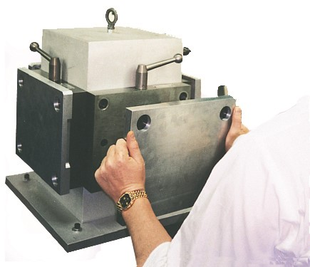 Operator lifting square aluminum micro pallet off a workholding tombstone